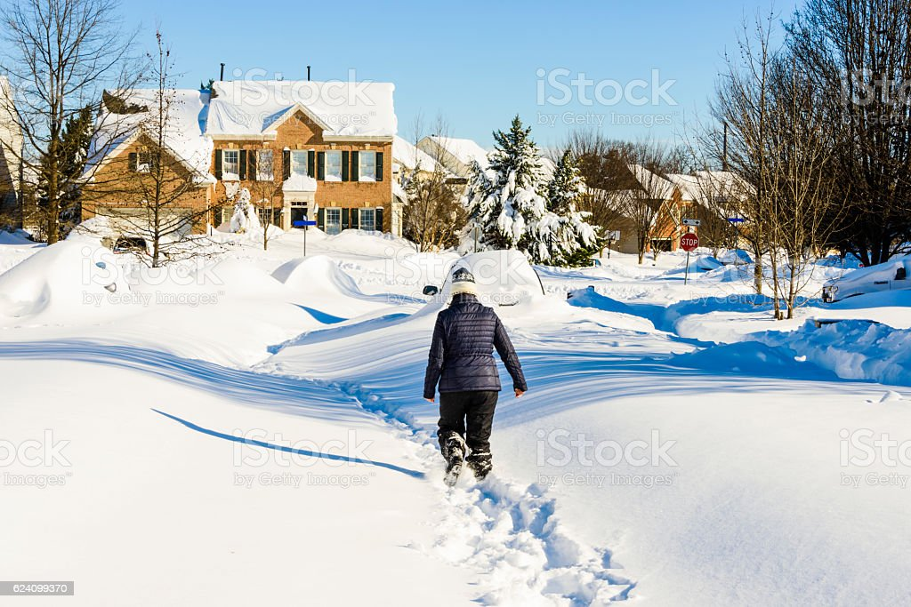 Woman walking through the street covered in deep snow. stock photo
