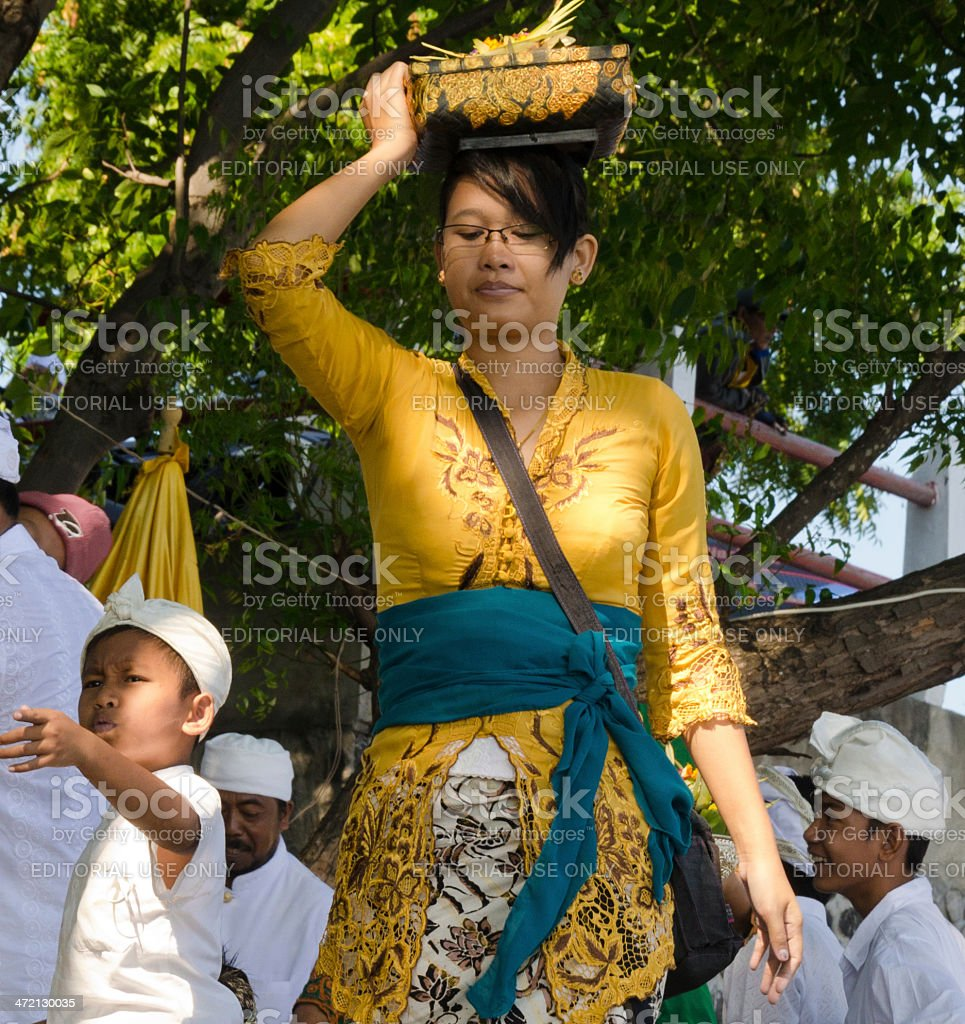 woman walking to a temple ceremony in Bali - Indonesia royalty-free stock photo