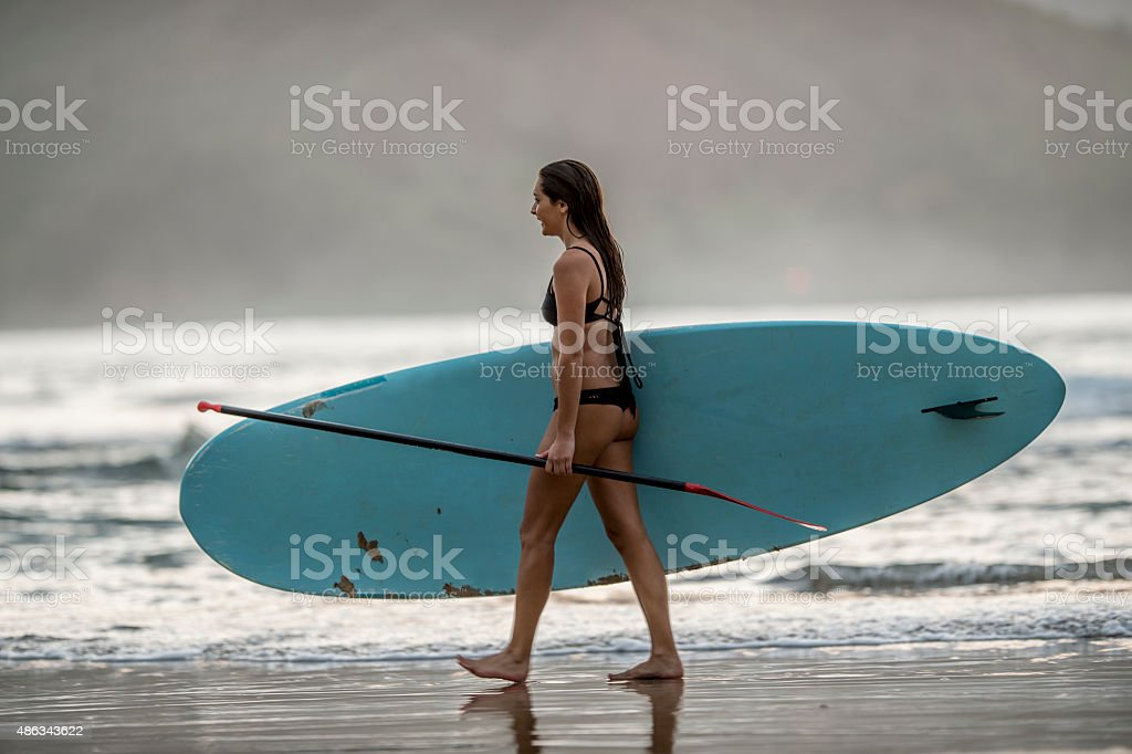 Woman Walking to the Ocean with a Paddle Board stock photo