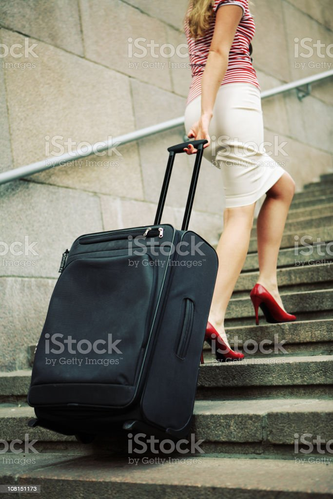 Woman Walking Up Outdoor Stairs with Rolling Suitcase royalty-free stock photo