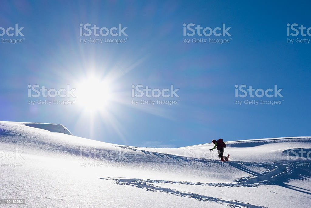 Woman walking up snowy hillside stock photo