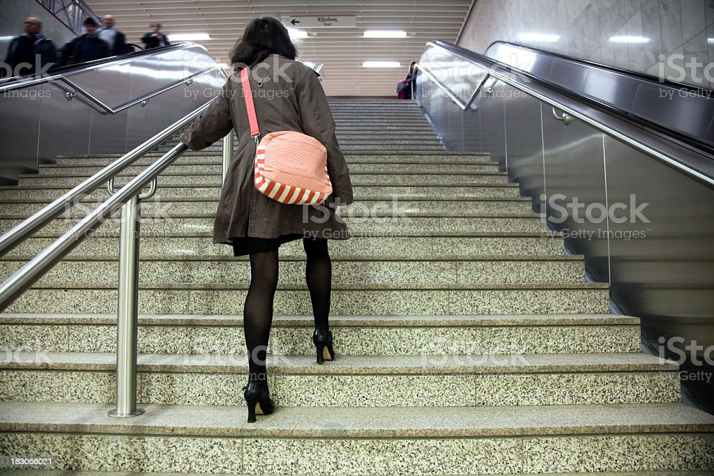 Woman walking up stairs with escalators on either side stock photo