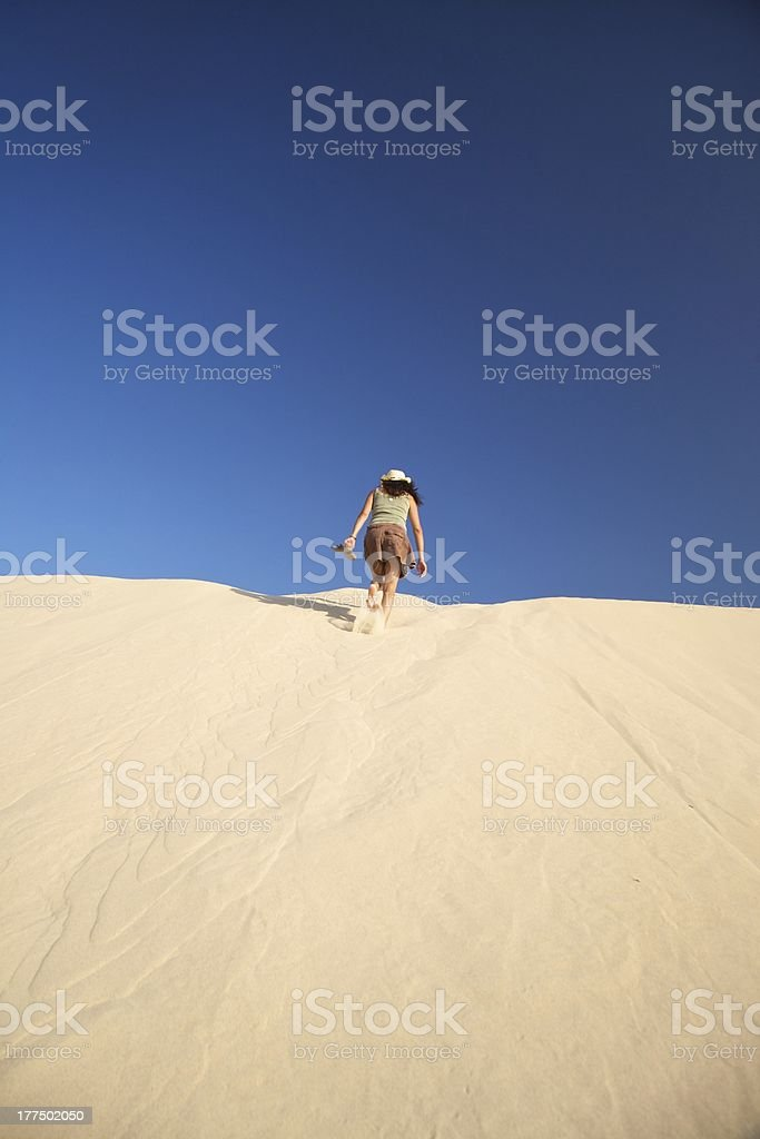 woman walking up the dune royalty-free stock photo