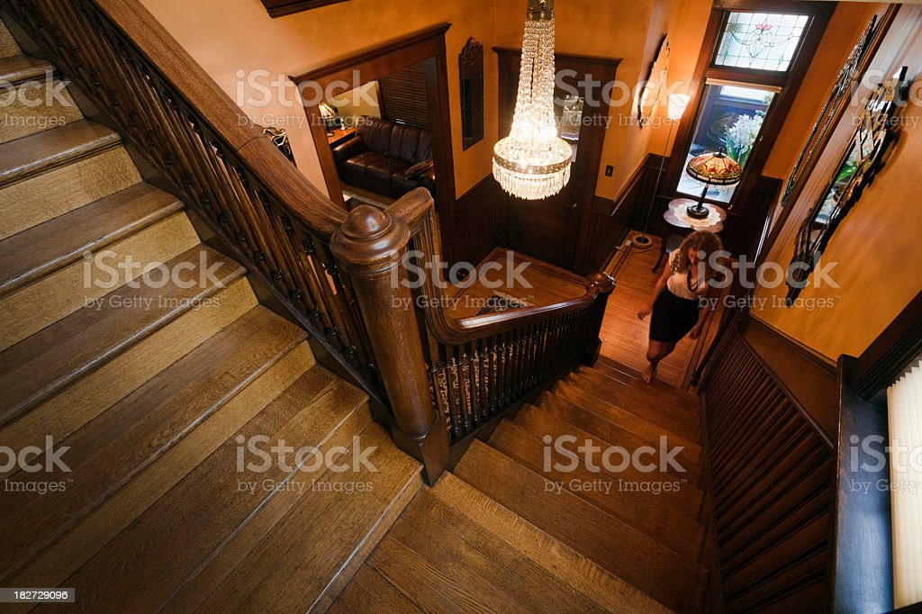 Woman Walking Up Wooden Staircase of Restored, Renovated Victorian Home royalty-free stock photo