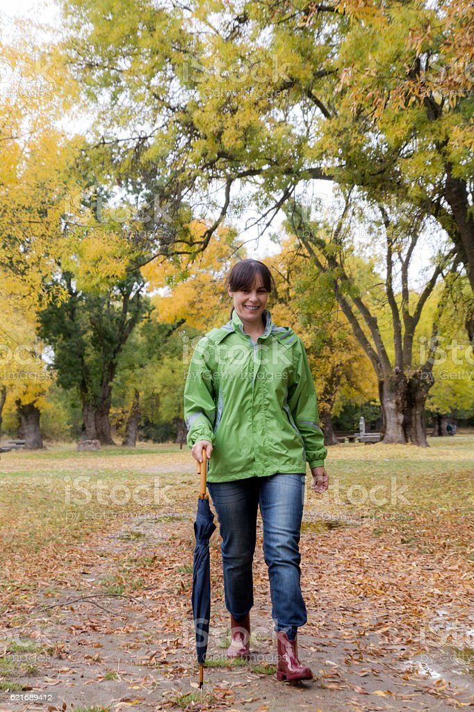 Woman walking with an umbrella in a park stock photo