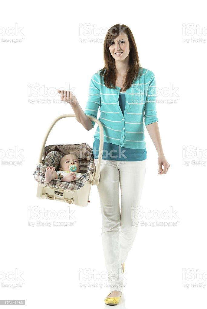 Woman walking with baby in carrier stock photo