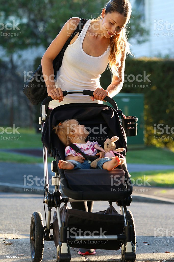 Woman walking with baby stroller stock photo