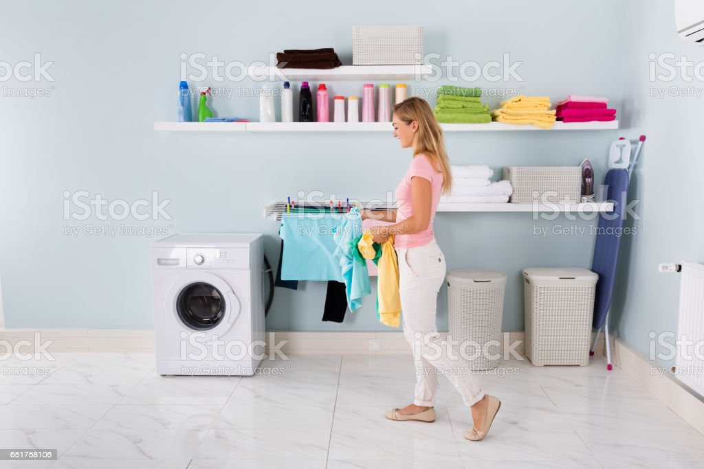 Woman Walking With Clothes In Utility Room stock photo