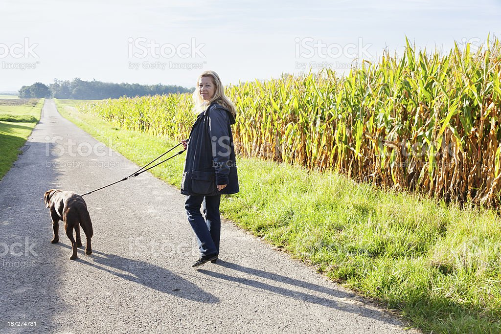 woman walking with dog healthy lifestyle royalty-free stock photo