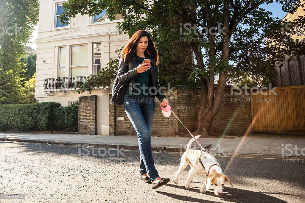 Woman walking with dog in early Sunday morning in London stock photo