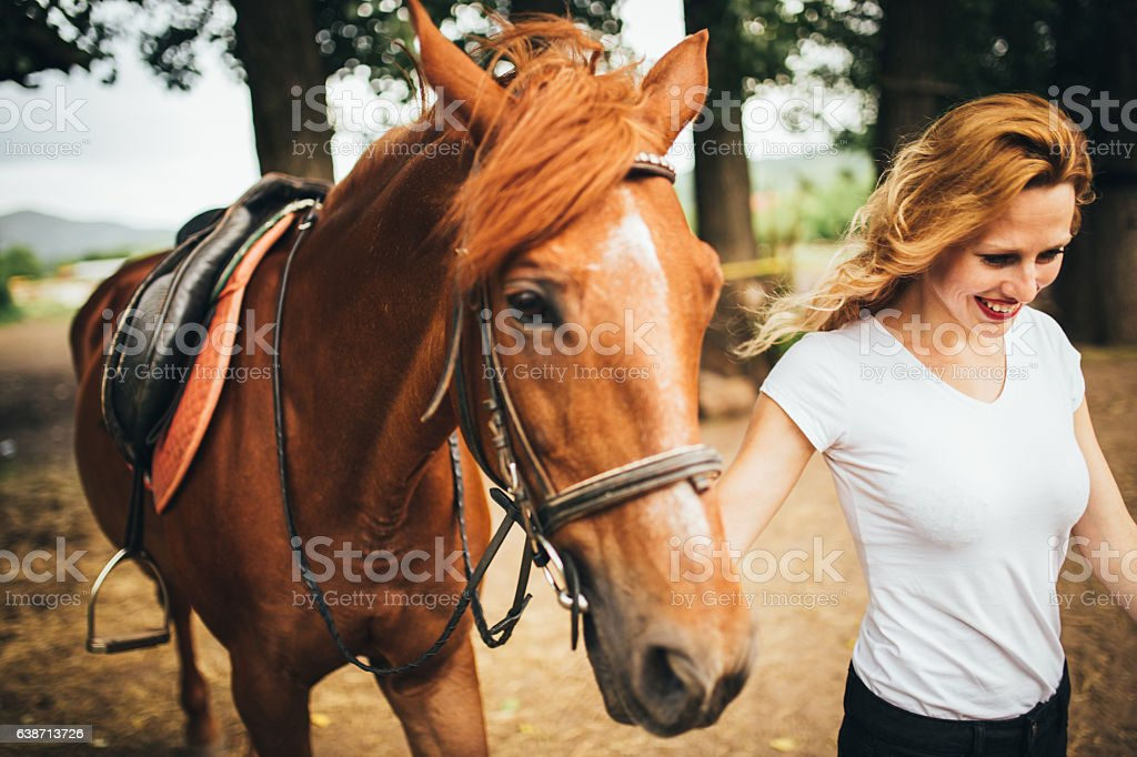 Woman walking with horse stock photo