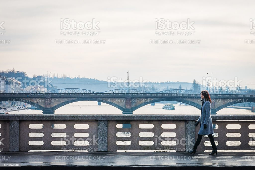 Woman walks across the Vltava River in Prague stock photo