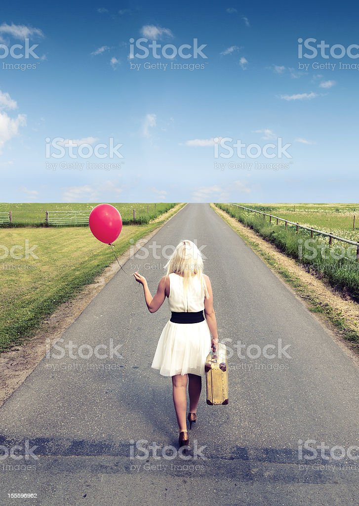 Woman walks away while holding balloon and suitcase royalty-free stock photo