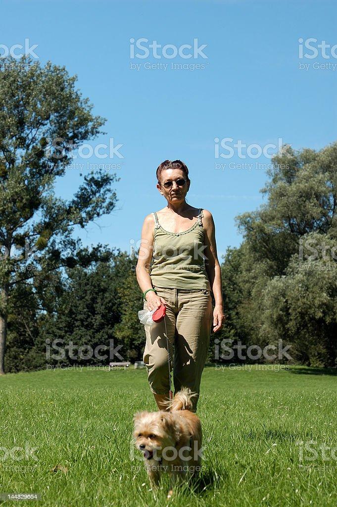 Woman walks her dog royalty-free stock photo