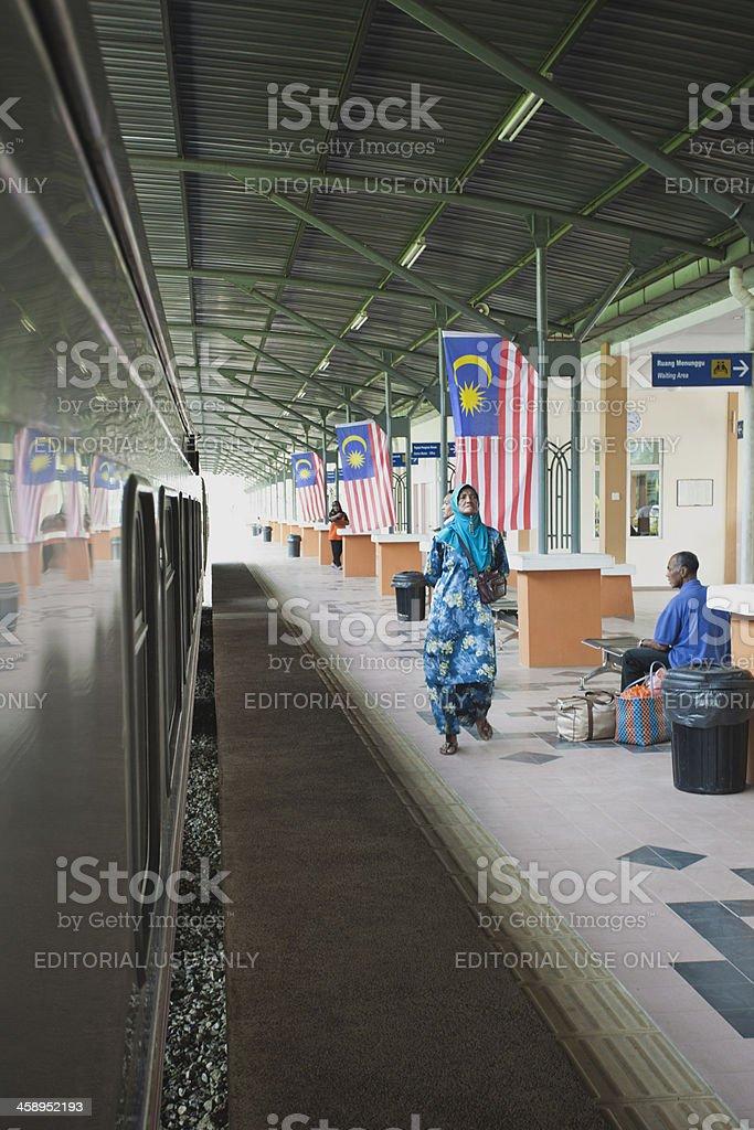 Woman walks in a Malay train station. stock photo