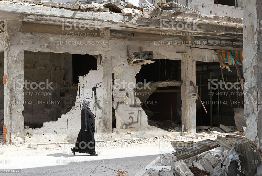 Woman walks near destroyed homes in Homs stock photo
