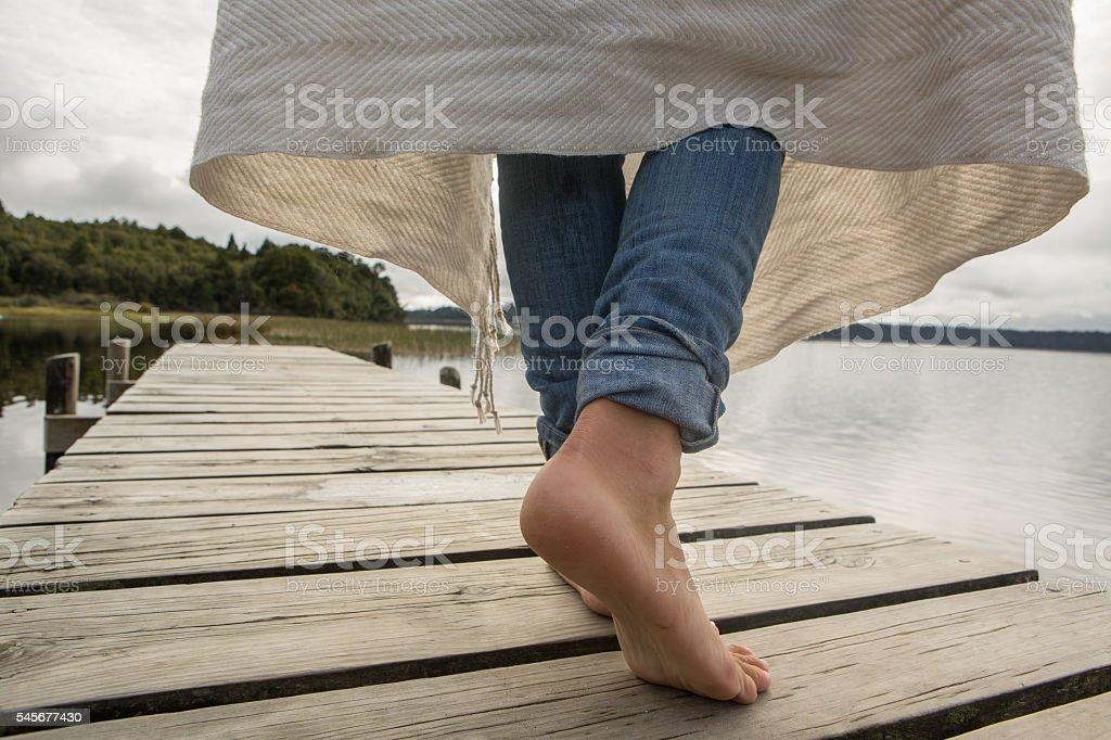 Woman walks on jetty above lake stock photo