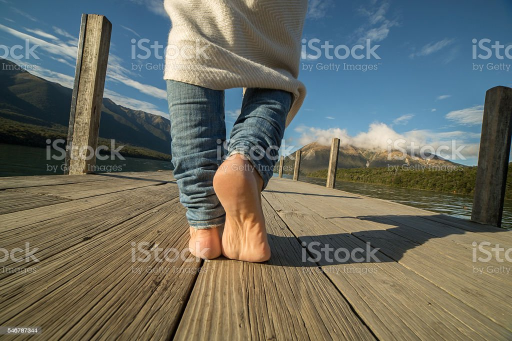 Woman walks on wooden pier above lake stock photo