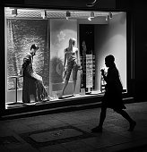 Woman walks past shop window with mannequins