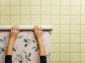 Woman wallpapering wall, close-up