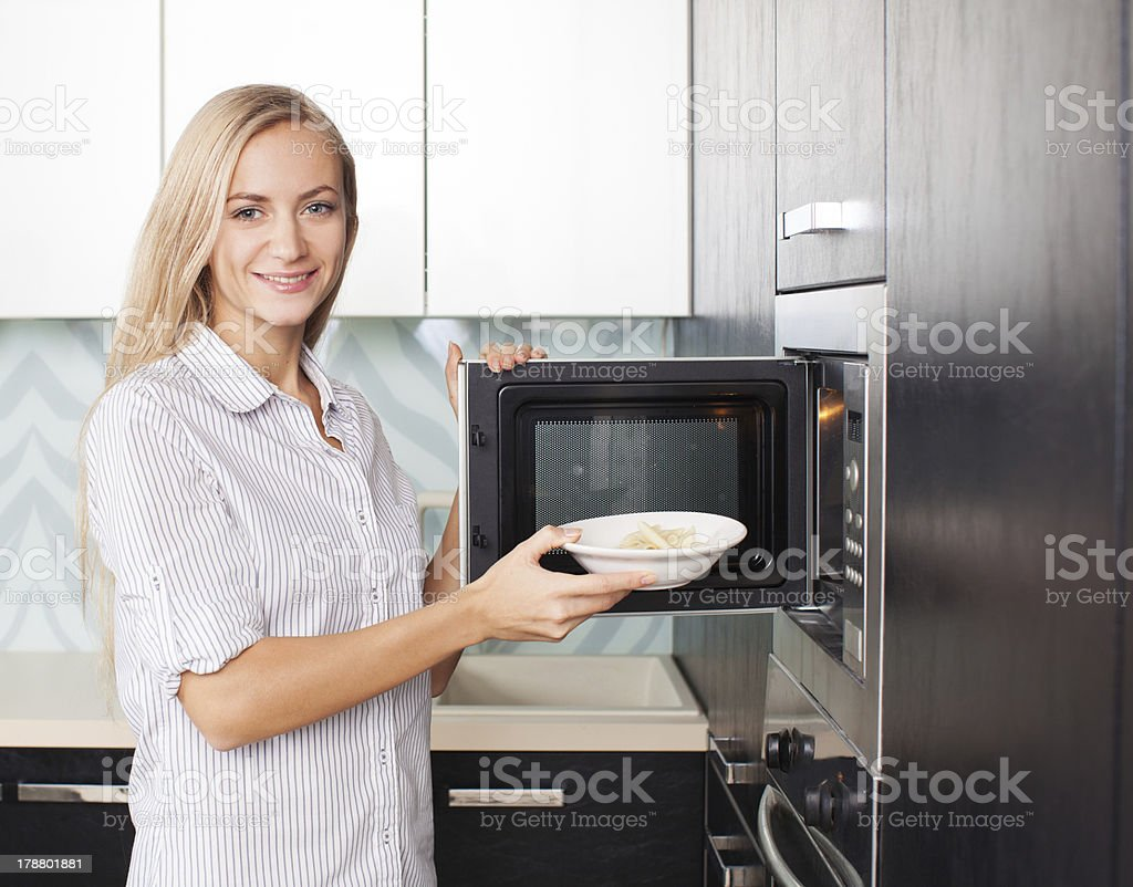 Woman warms up food in the microwave stock photo