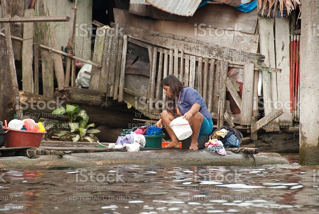 Woman washes clothes on water street of Belen, Iquitos, Peru. stock photo