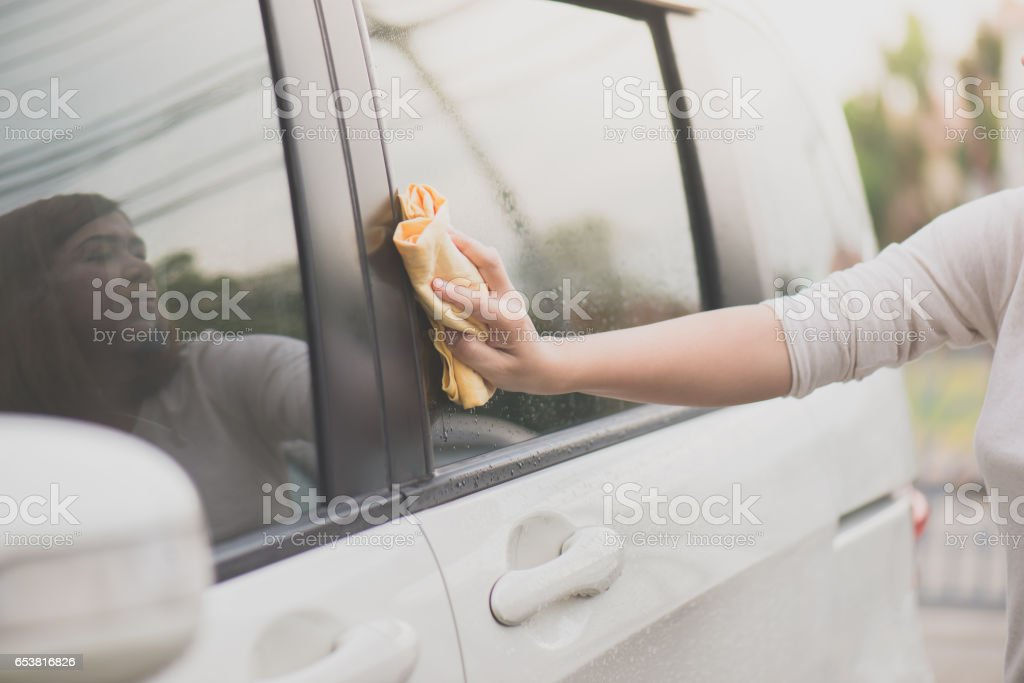 woman washing car window with microfiber cloth stock photo
