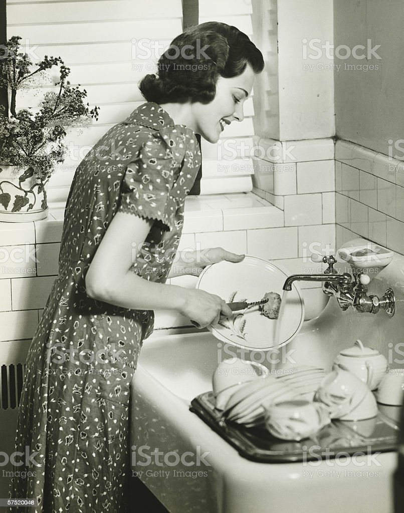 Woman washing dishes at kitchen sink, (B&W) stock photo