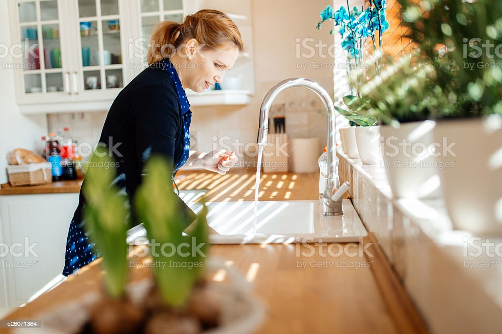 Woman washing dishes in kitchen stock photo