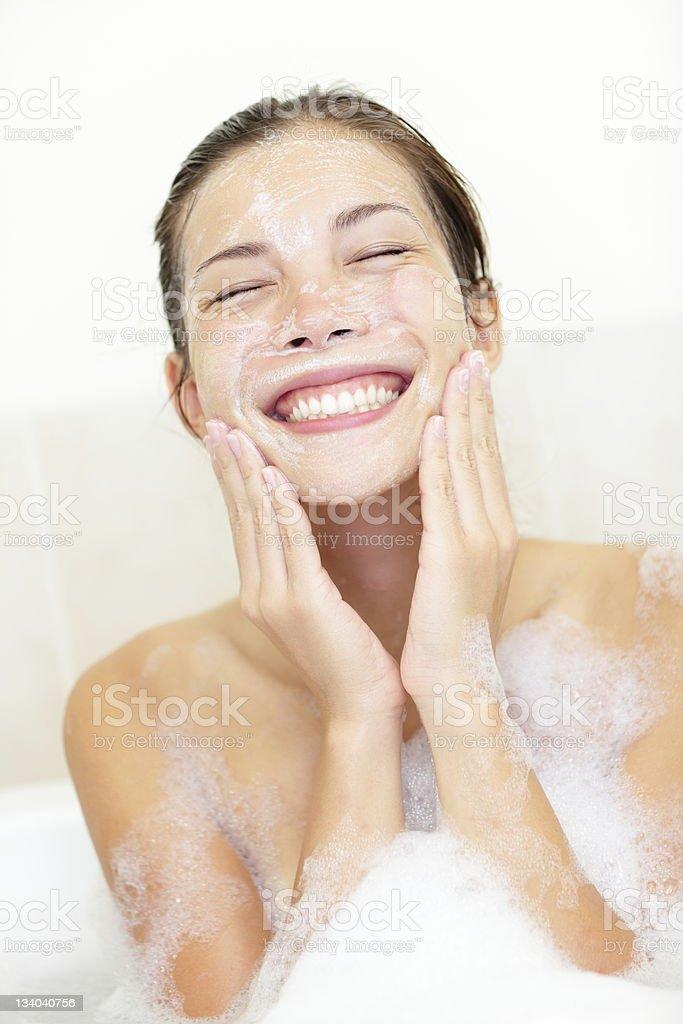 Woman washing face in bath stock photo