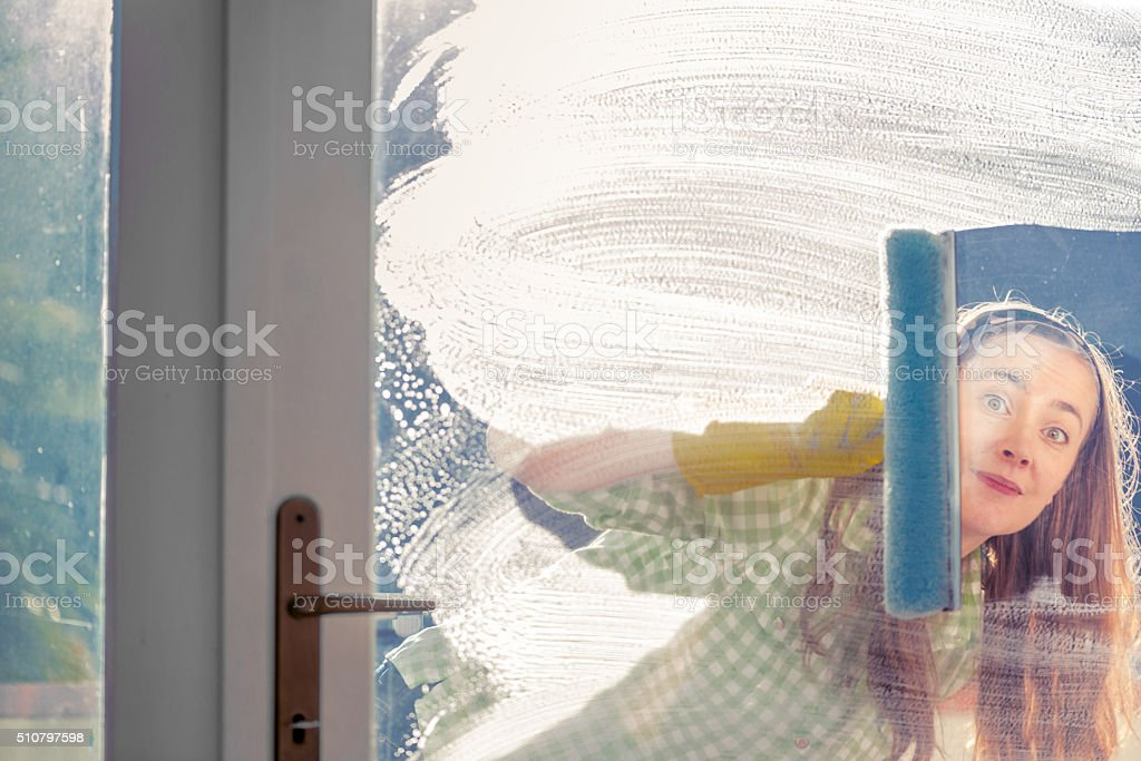 Woman Washing Glass Door with Squeegee and Peeking Through Window stock photo