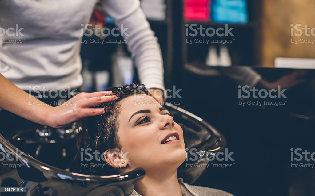 Woman washing hair at hairdressers stock photo