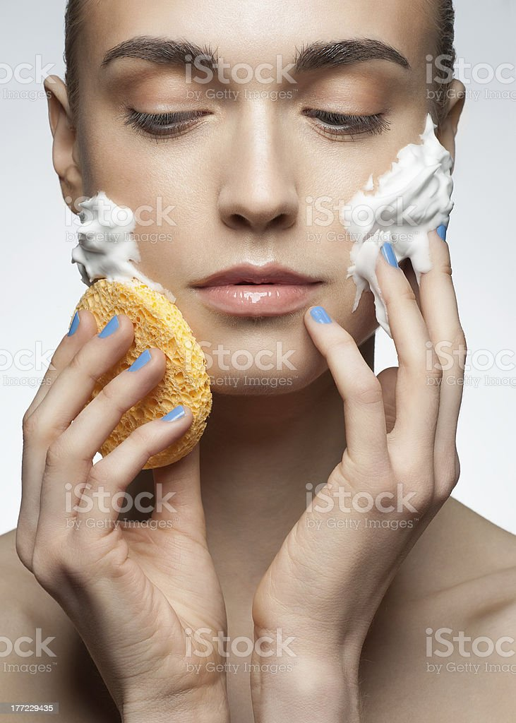 Woman washing her face with a yellow sponge royalty-free stock photo
