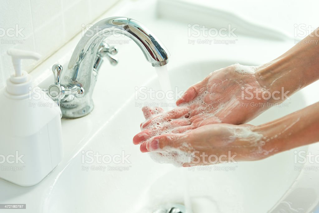 Woman washing her hands with soap and water at a sink stock photo