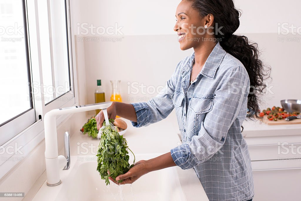 Woman washing parsley under faucet with cold water. stock photo