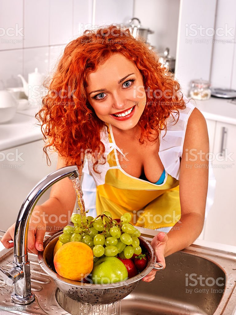 Woman washing vegetables at kitchen. stock photo