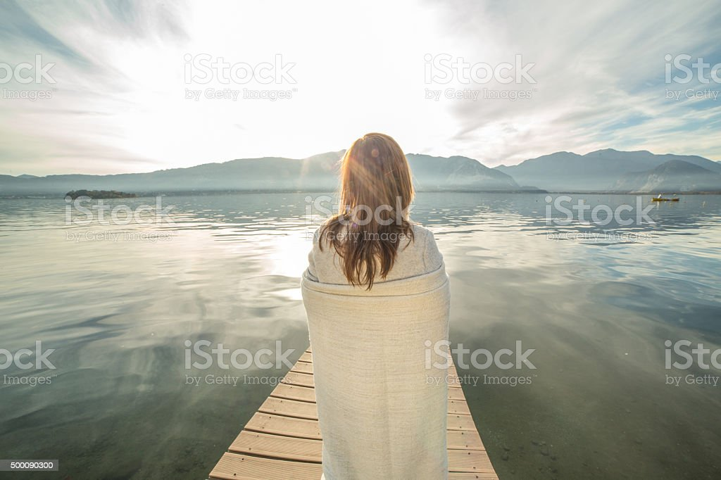 Woman watches sunset from lake pier, wrapped in blanket stock photo