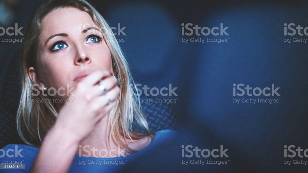 Woman watching a movie at movie theater. stock photo