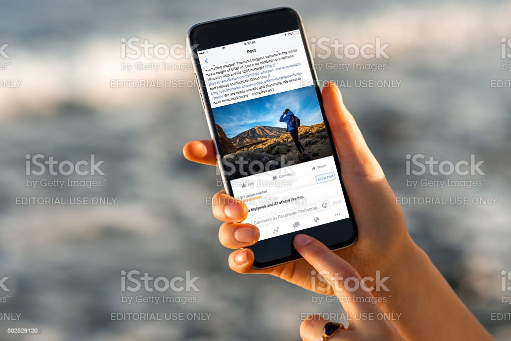 Woman watching Facebook news with new iPhone stock photo