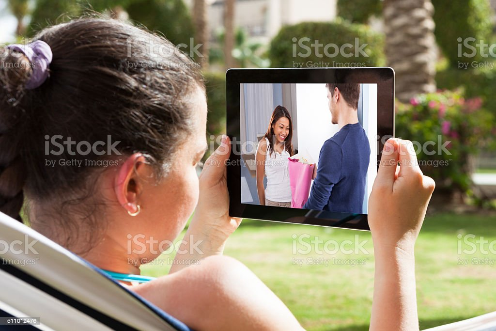 Woman Watching Movie On Digital Tablet stock photo