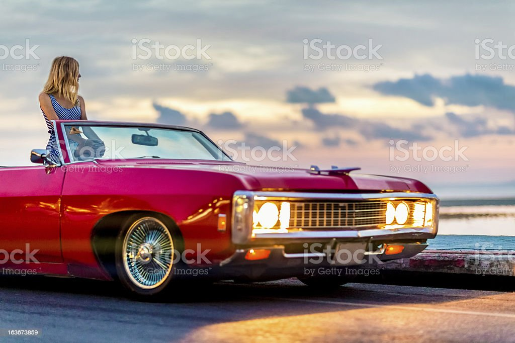 Woman watching sunset in retro car royalty-free stock photo