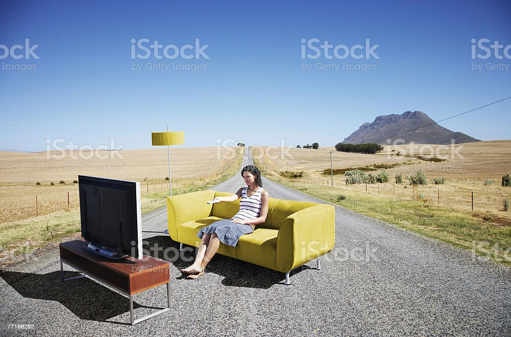 A woman watching television on a couch in the road stock photo