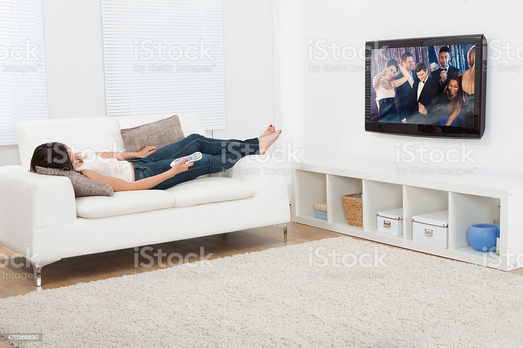 Woman Watching Television While Lying On Sofa stock photo