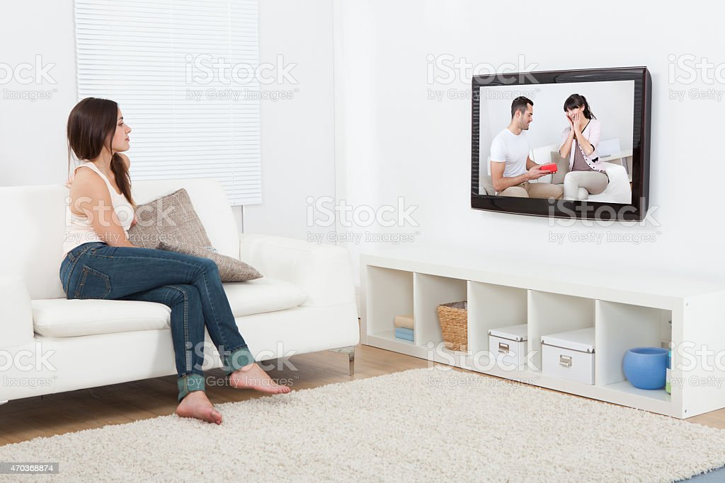 Woman Watching Television While Sitting On Sofa stock photo
