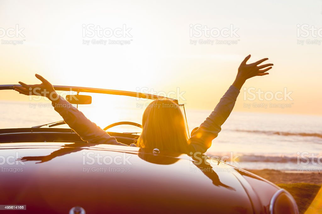 Woman watching the sunset in a convertible car. stock photo