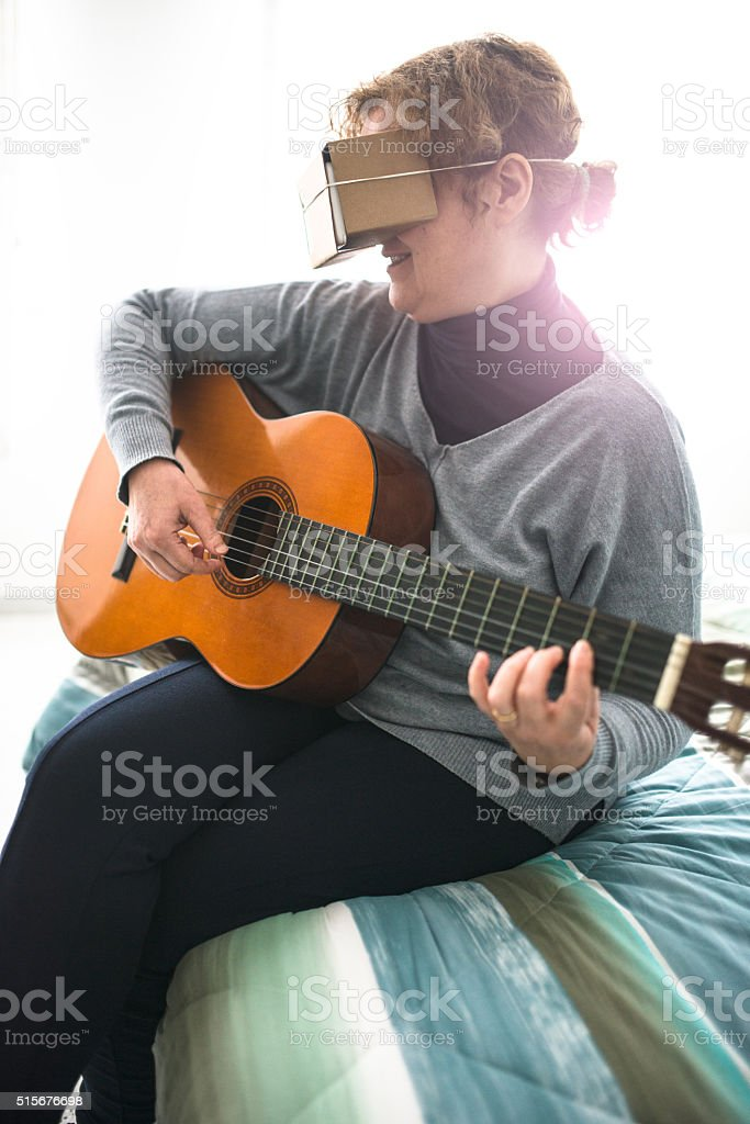 woman watching the virtual reality device simulator with guitar stock photo