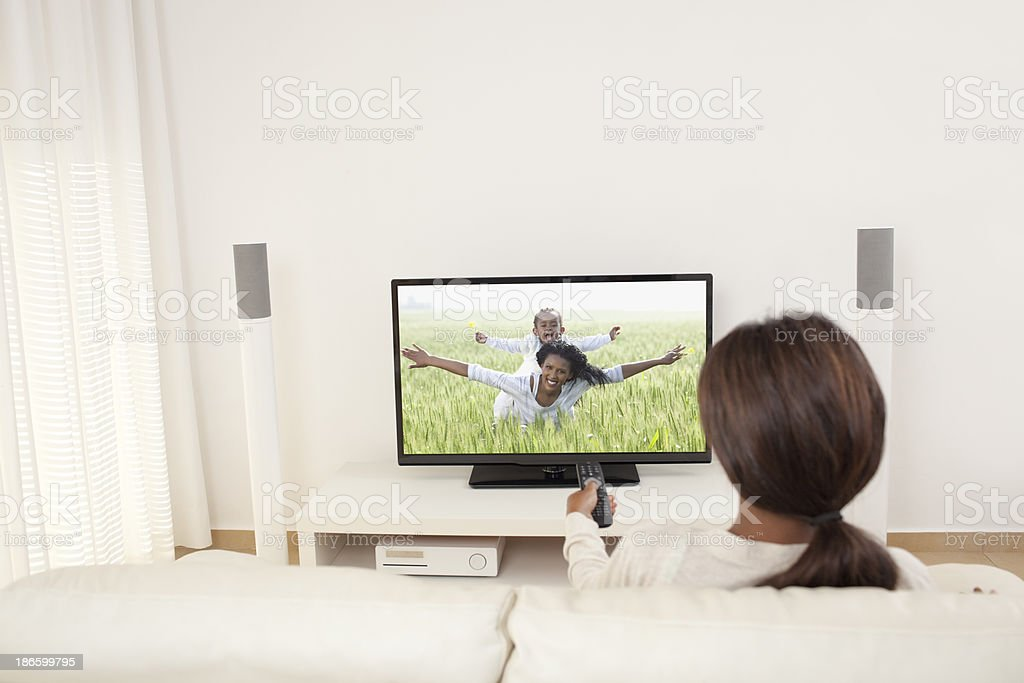 Relaxed woman watching TV in living room, on TV pic of mother and...