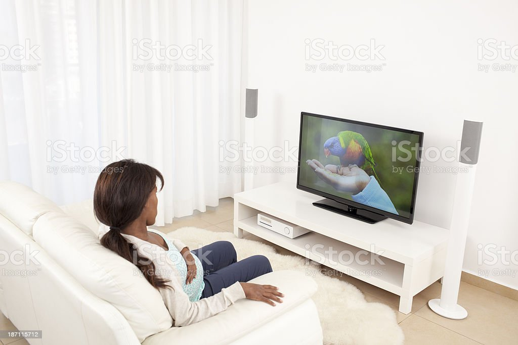 Relaxed woman watching TV in living room, on TV picture of parrot