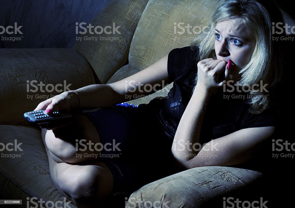Woman watching TV engrossed with fear and anticipation stock photo