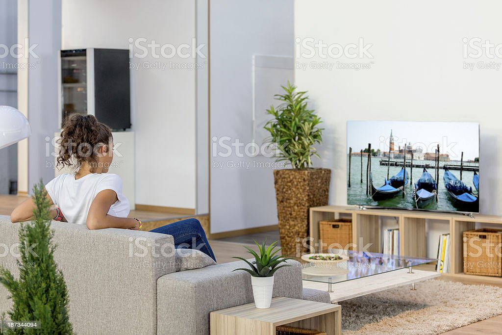 Woman watching tv in a modern, bright room stock photo